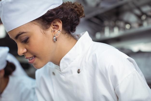 Primo piano del cuoco unico femminile in cucina