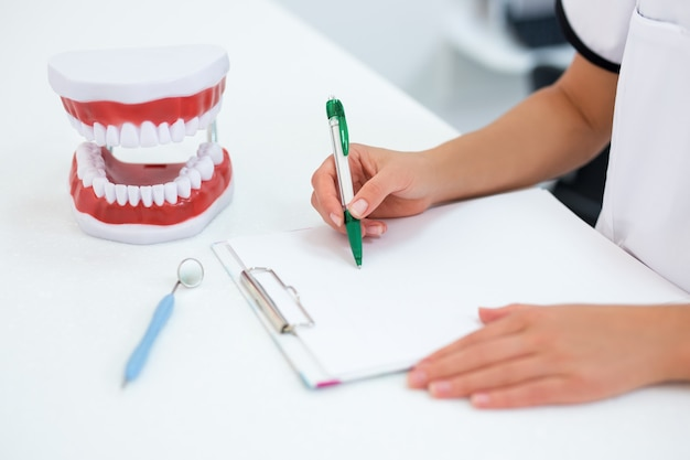 Primo piano delle mani del dentista femminile che scrivono qualcosa negli appunti con spazio di copia