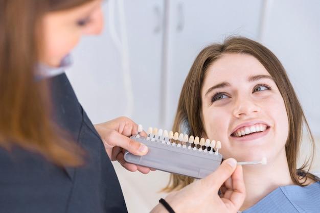 Primo piano di un dentista femminile con i campioni di colore del dente che scelgono l'ombra per i denti pazienti