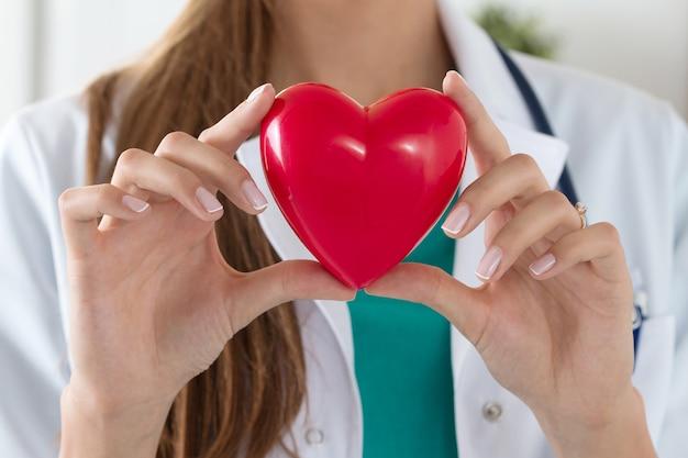 Primo piano delle mani di medico femminile che tengono cuore letto. assistenza sanitaria, cardiologia e concetto medico