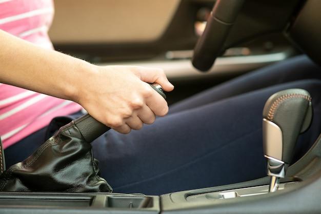 Chiuda in su del freno a mano femminile della holding della mano dell'autista in un'automobile.