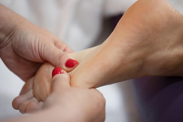 Primo piano del piede femminile nelle mani di un massaggiatore rilassante massaggio ai piedi in un salone spa.
