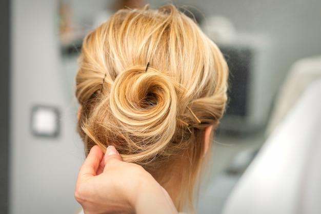 Chiuda in su del parrucchiere femminile per lo styling dei capelli biondi di una giovane donna in un salone di bellezza