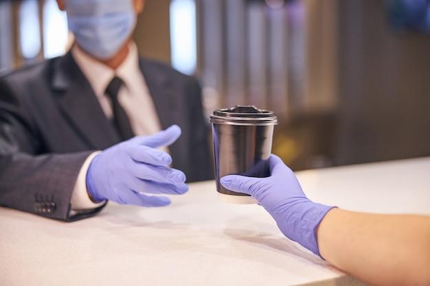 Primo piano della mano femminile che dà caffè caldo a un uomo elegante al bar mentre l'uomo indossa maschera e guanti in lattice