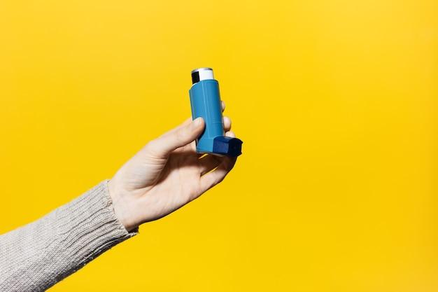 Primo piano della mano femminile che tiene l'inalatore asmatico sulla superficie gialla.