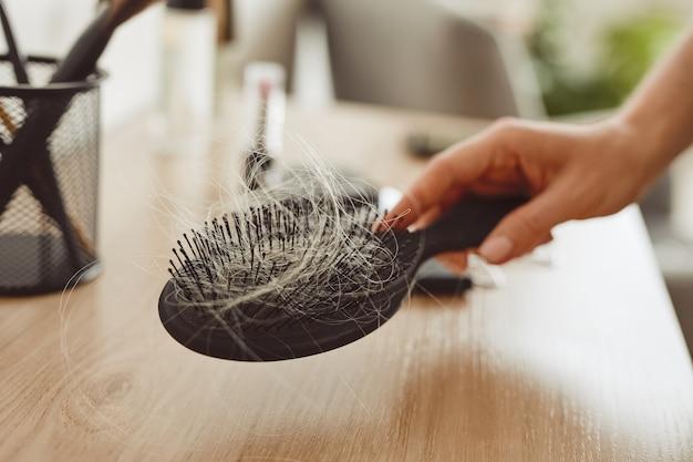 Primo piano della mano femminile che tiene la spazzola piena di capelli, perdita di capelli e concetto di alopecia, copia dello spazio