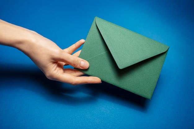 Primo piano della mano femminile che tiene una busta del libro verde