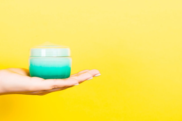 Stretta di mano femminile che tiene un vasetto di cosmetici su sfondo giallo