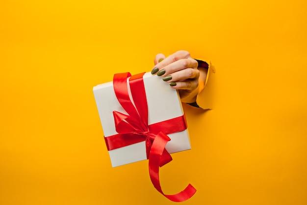 Il primo piano della mano femminile che tiene un regalo attraverso una carta gialla strappata, isolata
