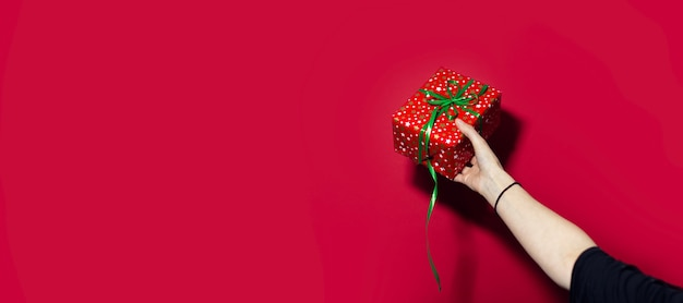 Primo piano della mano femminile che tiene un contenitore di regalo rosso isolato sulla superficie rossa con lo spazio della copia.