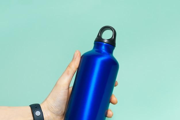 Primo piano della mano femminile che tiene un eco riutilizzabile, bottiglia di acqua termale in alluminio di colore blu fantasma, isolato su aqua menthe