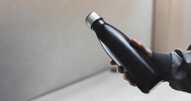 Primo piano della mano femminile che tiene la bottiglia di acqua termica riutilizzabile in acciaio eco di nero sulla superficie del tavolo per ufficio.