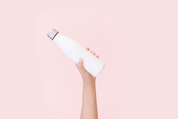 Primo piano della mano femminile che tiene riutilizzabile, bottiglia di acqua termica eco in acciaio di bianco, isolato su sfondo di colore rosa pastello. sii libero dalla plastica. zero sprechi. concetto di ambiente.