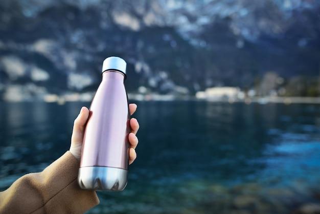 Primo piano della mano femminile che tiene la bottiglia riutilizzabile, in acciaio termo lucido per acqua, sullo sfondo dell'acqua limpida di un lago.