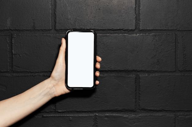 Primo piano della mano femminile che tiene uno smartphone con mockup, sullo sfondo del muro di mattoni nero.