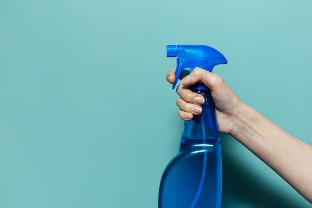 Primo piano della mano femminile che tiene il flacone spray per la pulizia con pompa blu