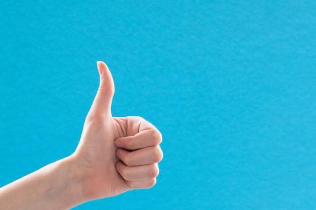 Mano femminile del primo piano che tiene il pollice sul segno della mano.