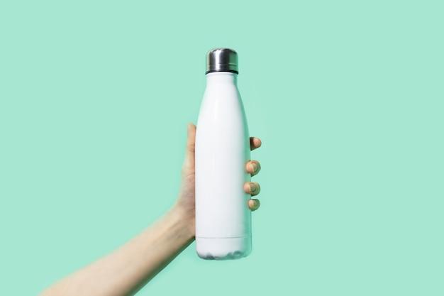 Primo piano della mano femminile che tiene la bottiglia di acqua termica riutilizzabile bianca di eco