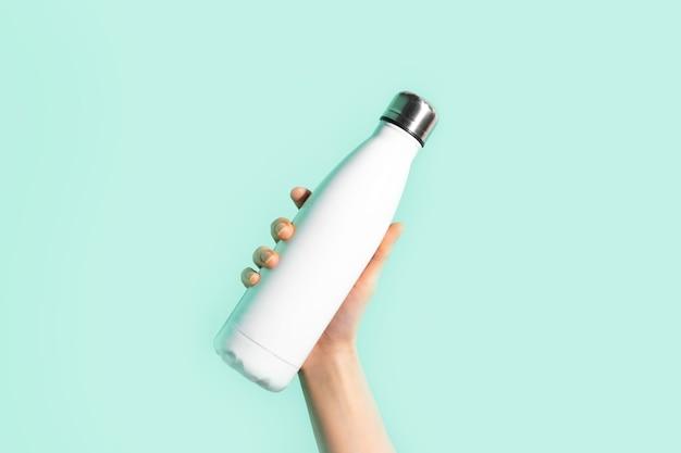 Primo piano della mano femminile, che tiene la bottiglia di acqua termica di eco inossidabile riutilizzabile bianca dell'acciaio inossidabile, isolata sulla parete del colore ciano, aqua menthe. sii libero dalla plastica. zero sprechi.