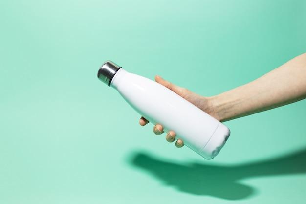 Primo piano della mano femminile che tiene la bottiglia di acqua termica inossidabile riutilizzabile bianca dell'acciaio inossidabile isolata sulla parete del colore dell'acqua menthe. senza plastica.