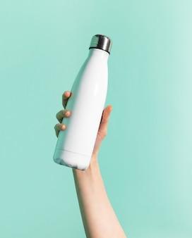 Primo piano della mano femminile che tiene la bottiglia di acqua termica inossidabile riutilizzabile bianca dell'acciaio inossidabile isolata sulla parete di colore ciano, aqua menthe. senza plastica.