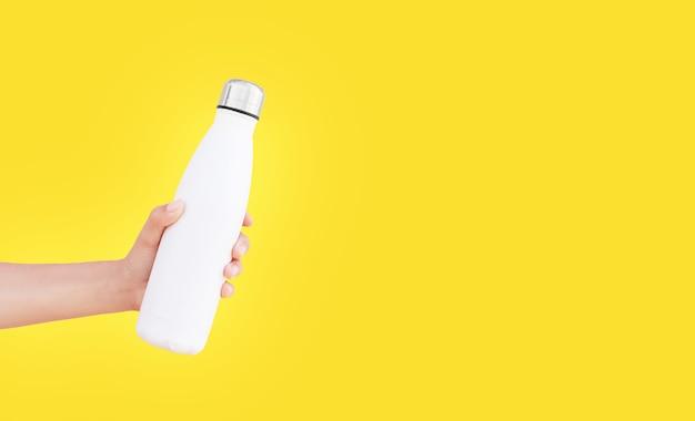 Primo piano della mano femminile che tiene la bottiglia di acqua termica d'acciaio riutilizzabile bianca isolata su di colore giallo con lo spazio della copia.