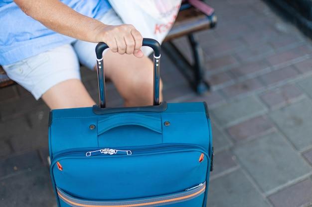 Primo piano della mano femminile tiene il manico di una valigia a mano mentre si attende un volo o un treno per viaggiare.