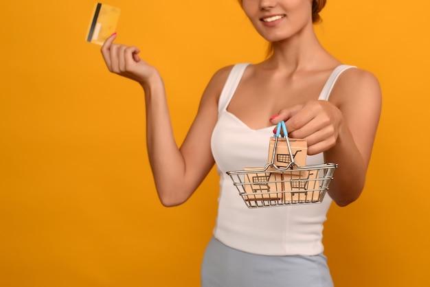 Primo piano della mano femminile orizzontale tiene il carrello in metallo giocattolo con manico in plastica blu e carta di credito isolato su sfondo. immagine