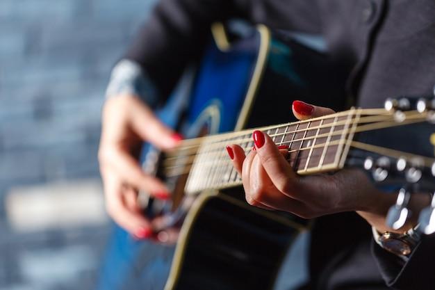 Mano femminile del primo piano che gioca sulla chitarra acustica.