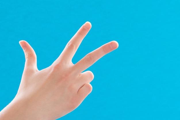 Mano femminile ravvicinata che mostra e punta verso l'alto con il numero tre dita su sfondo blu, copia dello spazio.