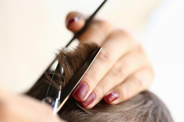 Primo piano della mano femminile che fa il taglio di capelli