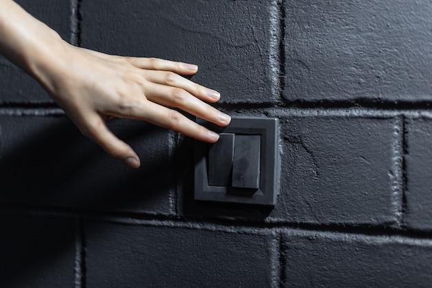 Primo piano della mano femminile, accendere / spegnere la luce tramite il pulsante dell'interruttore elettrico. sullo sfondo di un muro di mattoni neri.