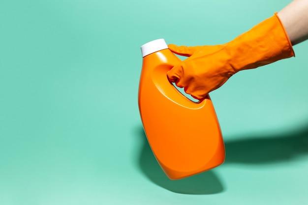 Primo piano della mano femminile che indossa il guanto di pulizia arancione, tenendo la bottiglia del detersivo sul colore aqua menthe della parete.