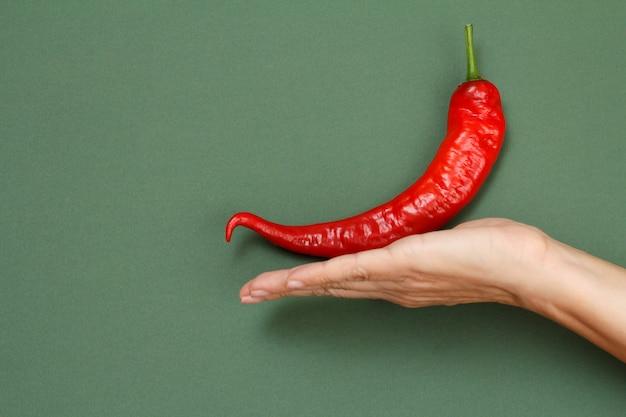 Chiuda sulla mano femminile con peperoncino rosso fresco su sfondo verde. vista dall'alto. concentrati sul pepe.