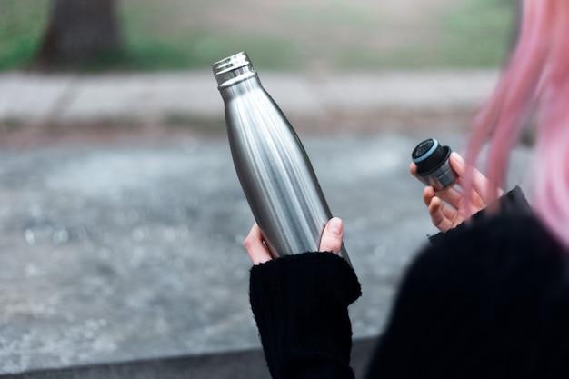 Primo piano della mano femminile con i capelli rosa, apri la bottiglia d'acqua termica eco riutilizzabile in acciaio.