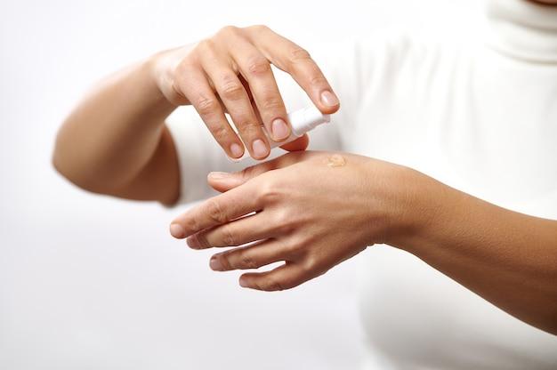 Primo piano delle mani femminili che applicano gel cosmetico trasparente sulle mani