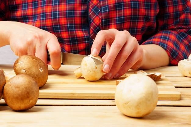 Primo piano delle mani femminili stanno tagliando i funghi su un tagliere. cucinare cibo.