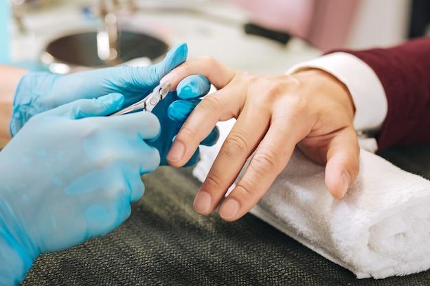 Primo piano di mani femminili vestirsi di guanti e utilizzando la presa della cuticola