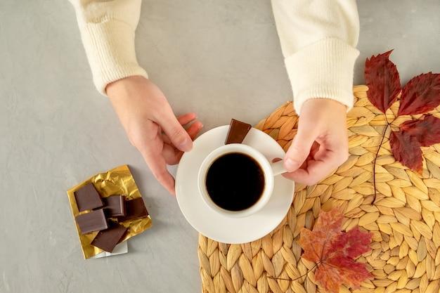 Il primo piano delle mani femminili tiene una tazza di caffè.
