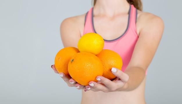 Chiuda sulle mani femminili che tengono i frutti e il limone delle arance isolati su gray