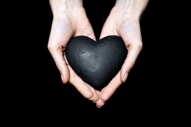 Primo piano delle mani femminili che tengono cuore nero