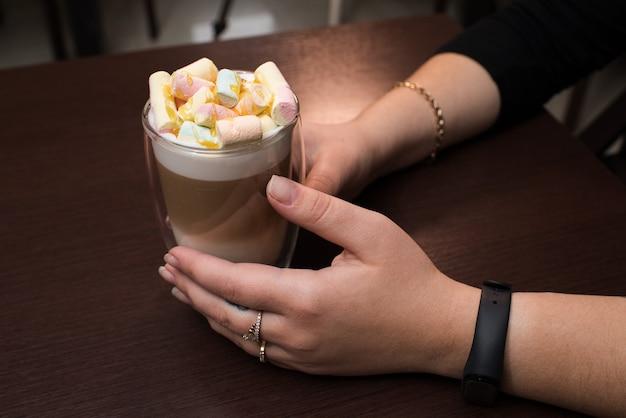 Mani femminili del primo piano che tengono il latte del caffè con marshmallow