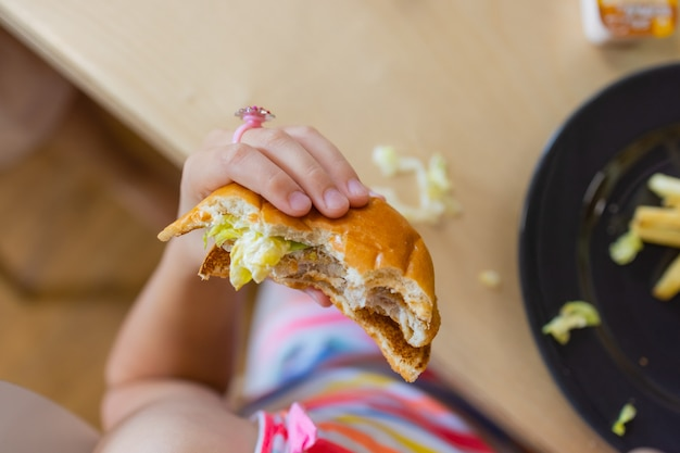 Primo piano delle mani femminili che tengono delizioso hamburger di bacon.