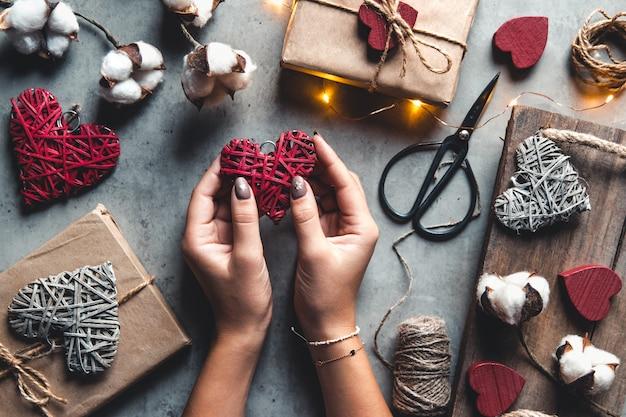 Primo piano sulle mani femminili che tengono un regalo in un cuore rosa presenta per san valentino, compleanno, festa della mamma. lay piatto. simbolo dell'amore. sfondo di san valentino con scatole regalo a bordo di cemento.