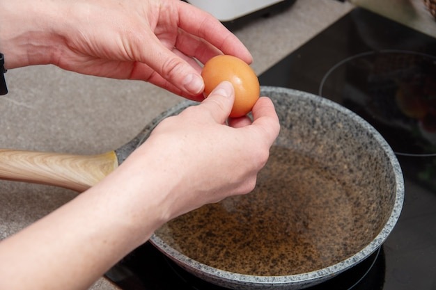 Mani femminili ravvicinate che tengono un uovo crudo su una padella, contenitore. messa a fuoco selettiva.