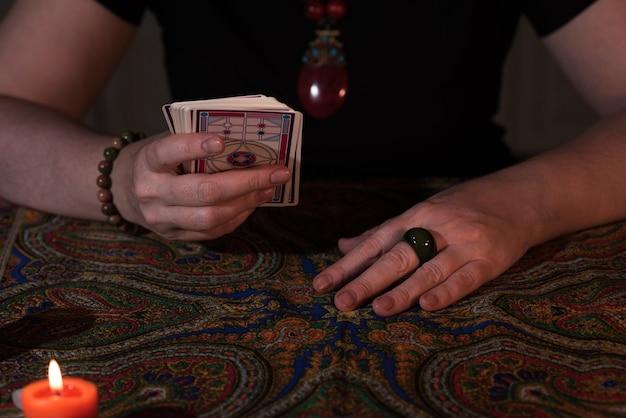 Chiuda sulle mani femminili che tengono i tarocchi. chiromante. stregoneria