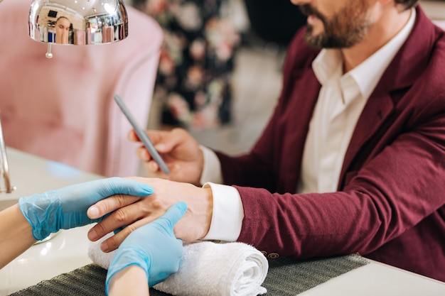 Chiuda in su delle mani femminili che idratano le mani maschili e si vestono con guanti blu