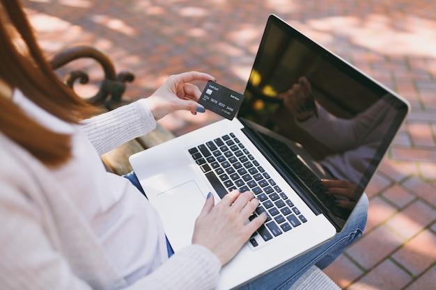 Chiuda sulle mani femminili sulla tastiera. donna seduta su una panchina in possesso di carta di credito, lavorando su un moderno computer pc portatile con schermo vuoto vuoto all'aperto. ufficio mobile. acquisti online, concetto di affari.