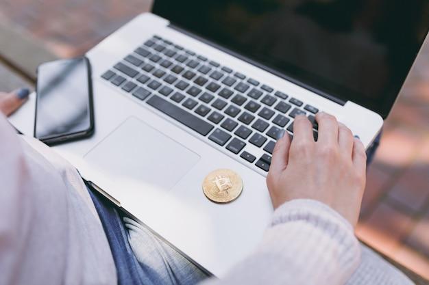 Chiuda sulle mani femminili sulla tastiera. donna seduta su una panchina che lavora su un computer portatile moderno con schermo vuoto vuoto per copiare lo spazio. bitcoin in strada all'aperto. ufficio mobile, concetto di valuta futura virtuale.