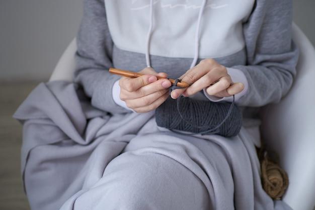 Primo piano delle mani femminili per maglieria all'uncinetto.